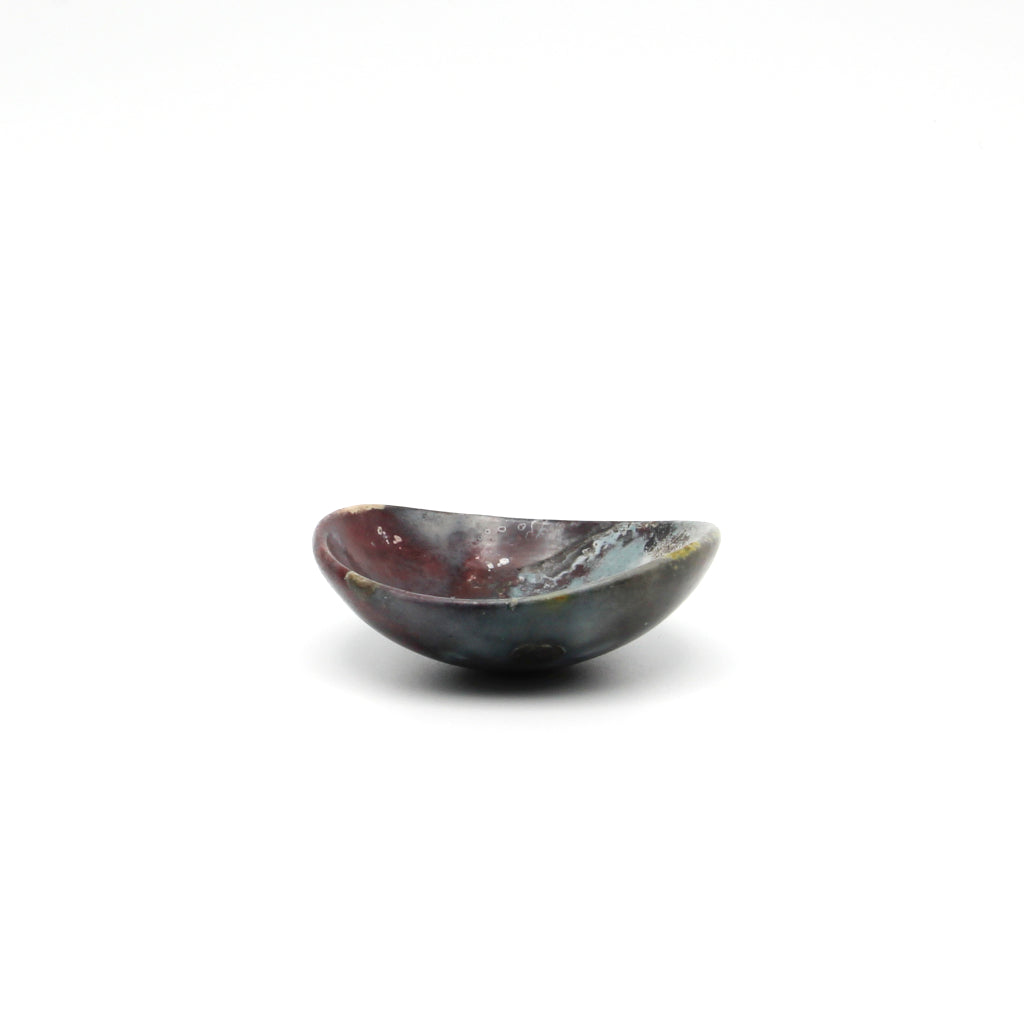 Kaolin - Kvalka -  Small and shallow smoke fired handmade ceramic bowl. View from one side. The colors inside the bowl are blue, black and burgundy hues