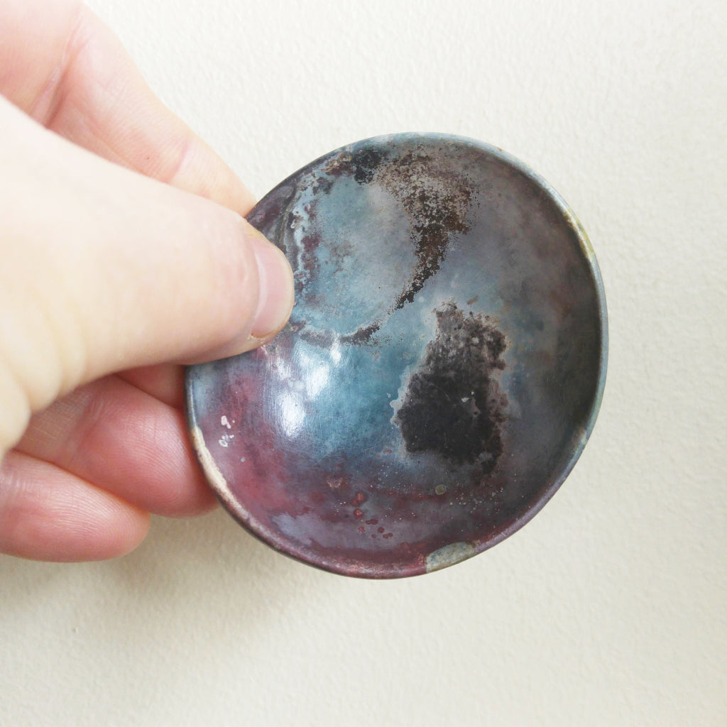 Kaolin - Kvalka - Randomly selected small and shallow smoke fired handmade ceramic bowl. Displayed in hand to show how small it is.