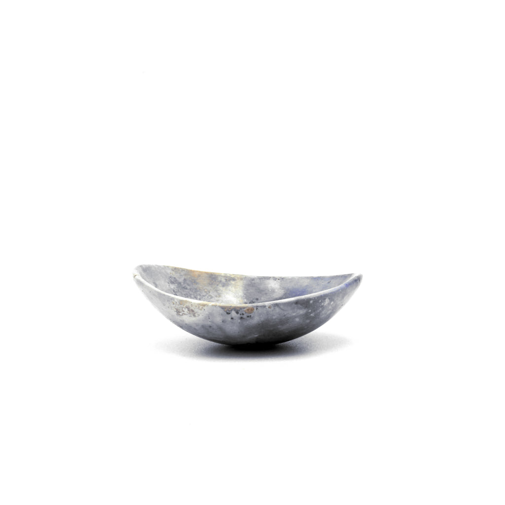 Kaolin - Kvalka -  Small and shallow smoke fired handmade ceramic bowl. The shape of the bowl is like the bottom of a sphere. The colors are blue, grey and white colors with hint of yellow.