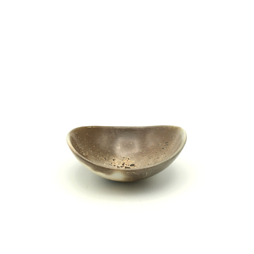 Kaolin - Kvalka -  Small and shallow smoke fired handmade ceramic bowl. View from one side. The colors inside the bowl are brown hues with black spots and hint of peach color in the bottom.
