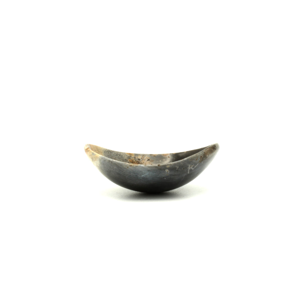 Kaolin - Kvalka -  Small and shallow smoke fired handmade ceramic bowl. The shape of the bowl is like the bottom of a sphere. The colors are hues of dark grey with  brown and light brown spots.