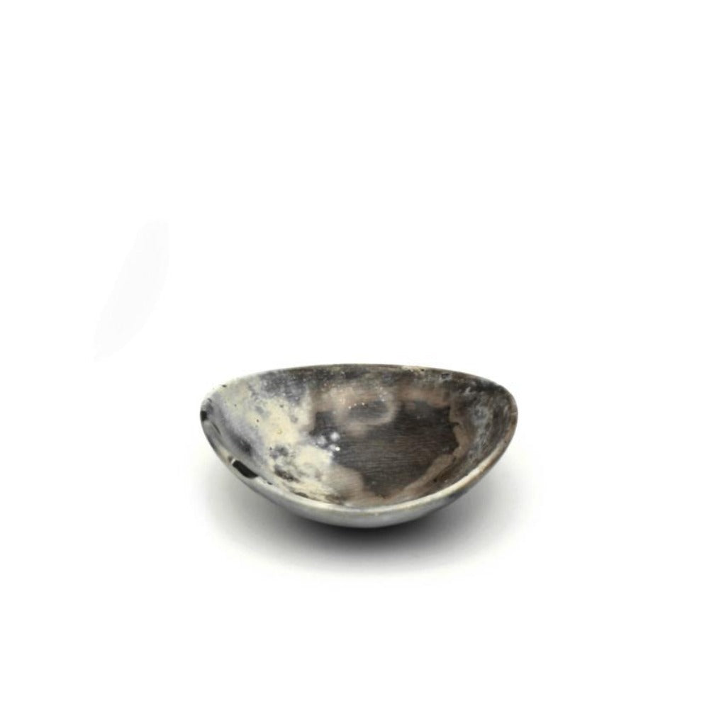 Kaolin - Kvalka - Small and shallow smoke fired handmade ceramic bowl. View from one side. The colors inside the bowl are Grey and white hues and small black spots on the edge.