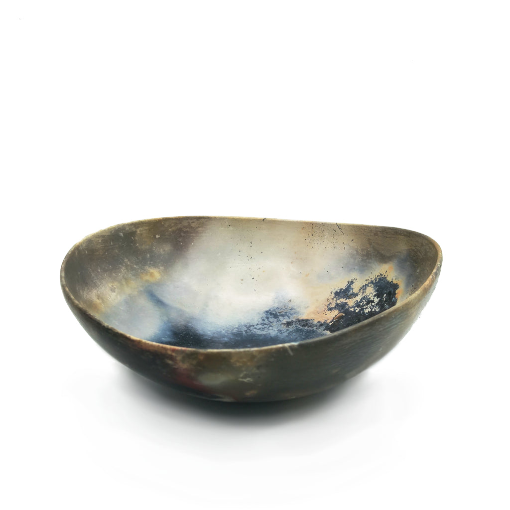 Kaolin - Kvalka - Deep smoke fired handmade ceramic bowl. View from one side. The colors inside the bowl are black, Smokey grey, light grey, yellow, red and orange splashes.