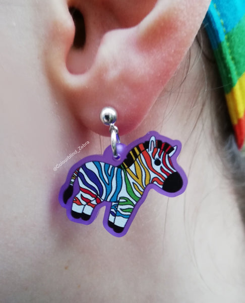 A photo of one rainbow zebra earring in my ear.