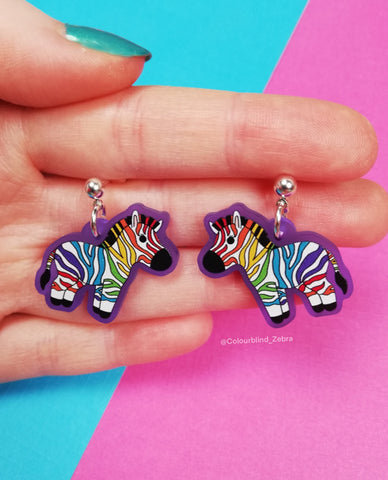A photo of me holding rainbow zebra earrings in my hand. The rainbow zebras are printed onto purple acrylic and the earring posts are silver plated.