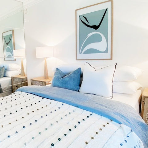 Stylish white blue & timber bedroom featuring abstract blue green black & white artwork by the paper tree