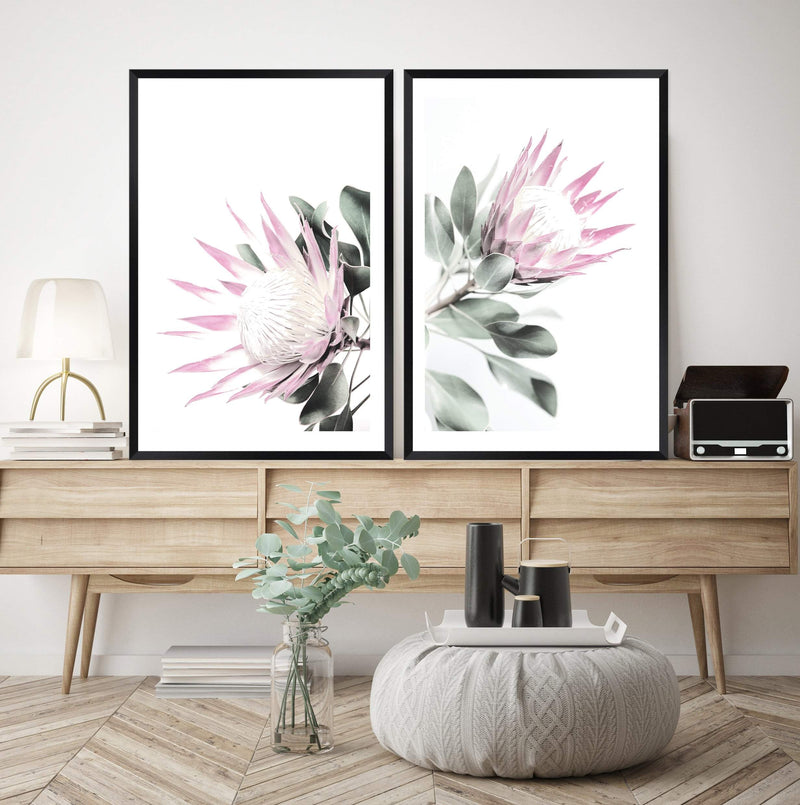 Set Of Two Pink King Protea Art Prints In Black Frames On A Buffet