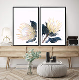 Set Of Two Yellow Protea Art Prints In Black Frames In a Lounge Room Over A Buffet