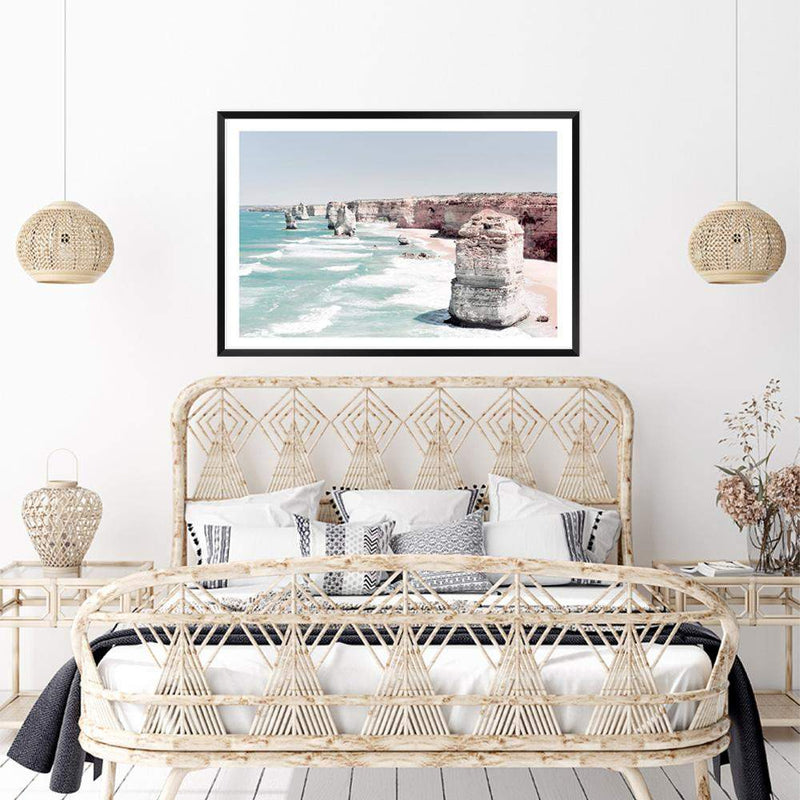 Coastal Art Print Of The Australian Landmark The Great Ocean Road & The Twelve Apostles Framed In A Black Timber Frame Above A Rattan Bed In A Coastal Themed Bedroom