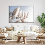 coastal art print featuring a photographed print of tall pampas grass with a neutral beach feel with a timber frame over a white sofa in a neutral lounge room