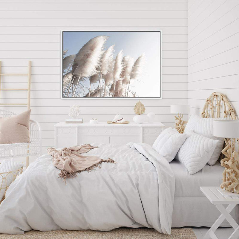 coastal art print featuring a photographed print of tall pampas grass with a neutral beach feel with a white frame in a coastal decorated bedroom