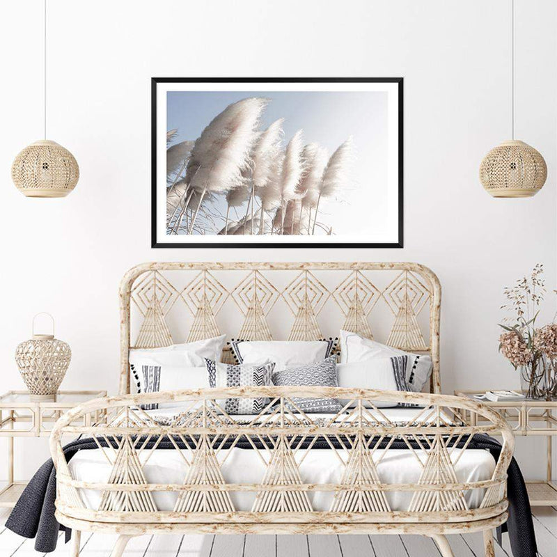 coastal art print featuring a photographed print of tall pampas grass with a neutral beach feel with a black timber frame over a rattan bed in a coastal beach house bedroom