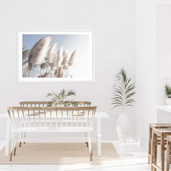 coastal art print featuring a photographed print of tall pampas grass with a neutral beach feel with a white timber frame in a coastal dining room above a white Ombre dining table