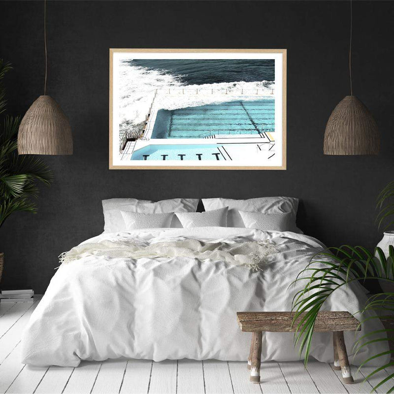 Photographed Print Of The Famous Australian Bondi Beach Ocean Pool In A Natural Timber Frame On A Charcoal Wall Above A White Bed