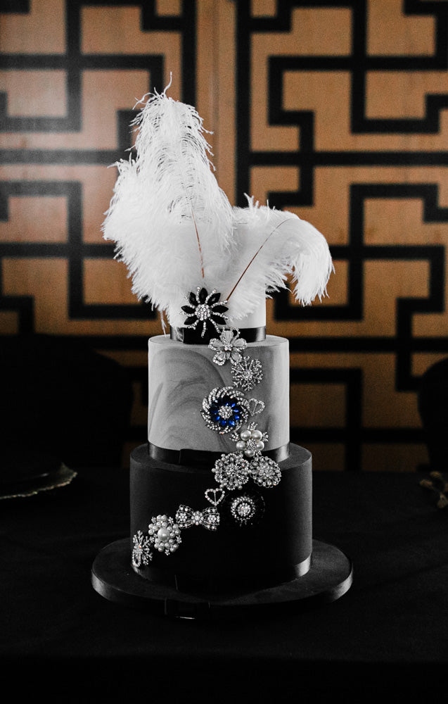 Bespoke three-tier wedding cake in Art Deco theme. Decorated with black ribbon and silver, blue and pearl floral motifs