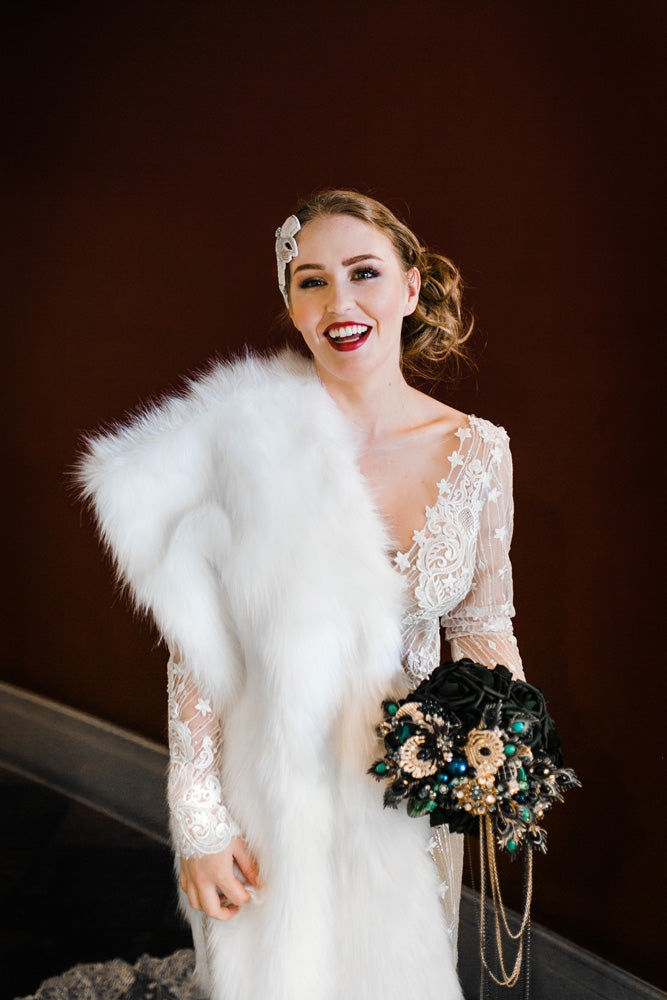 Bride with a bouquet of black roses, peacock feathers and bold beading.