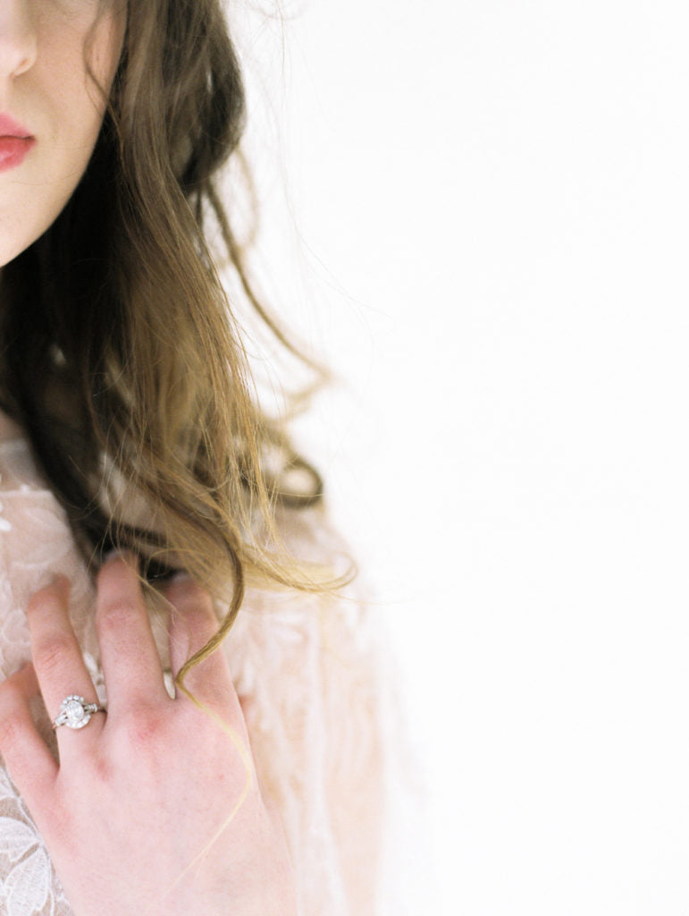 The 0.72 carat oval diamond ring is worn by the bride