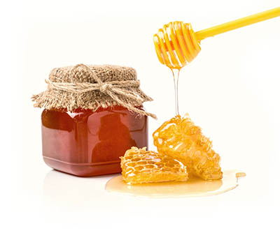 Fresh honey with honeycomb on white background.