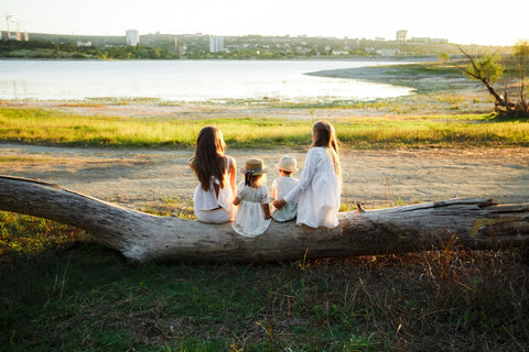 The family sits with their backs to the camera on a fallen log against the backdrop of the lake