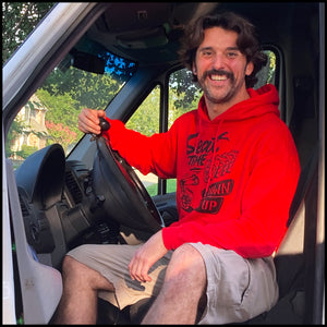 Lifestyle shot of Woody in his #MotoVan, showcasing the red One Down Five Up Hoodie.
