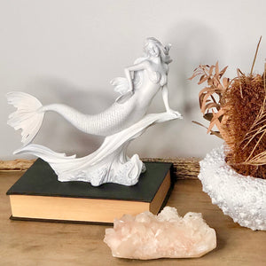 Mermaid riding wave statue