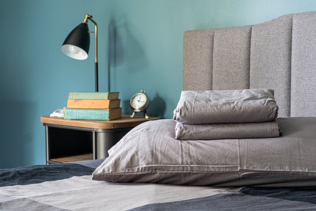 Grey sheet set on a bed for earthing real lifestyle