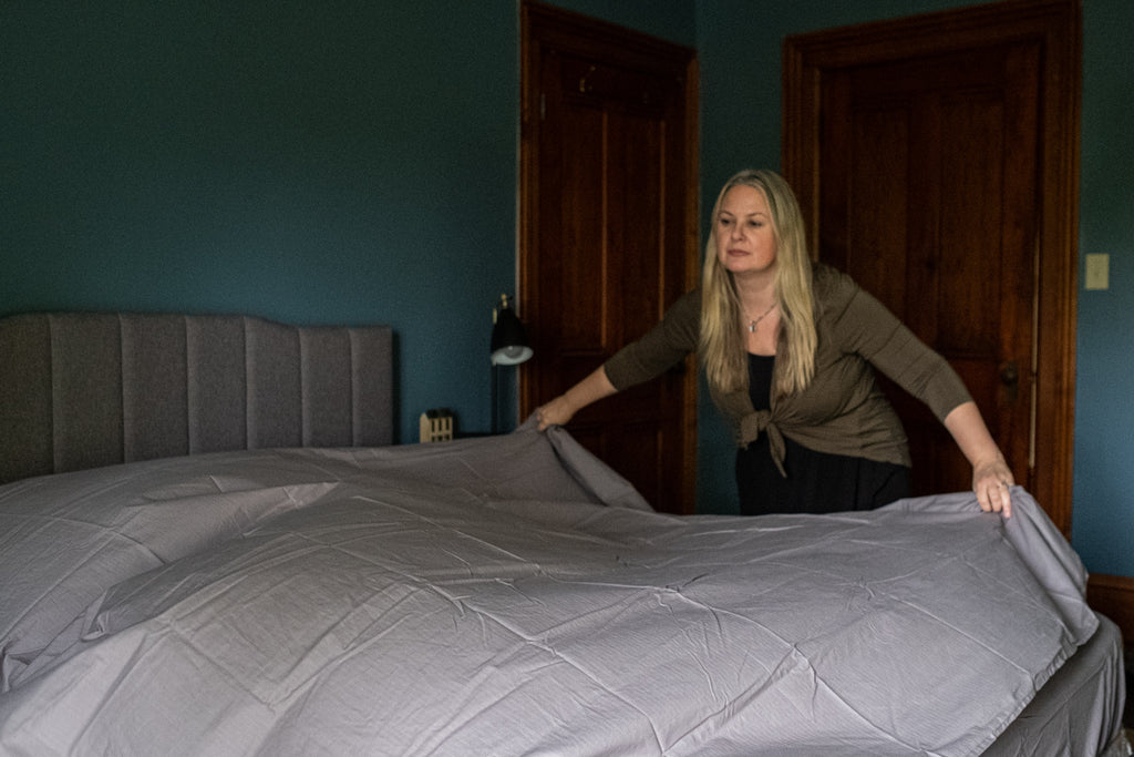 women making a bed with grey sheets