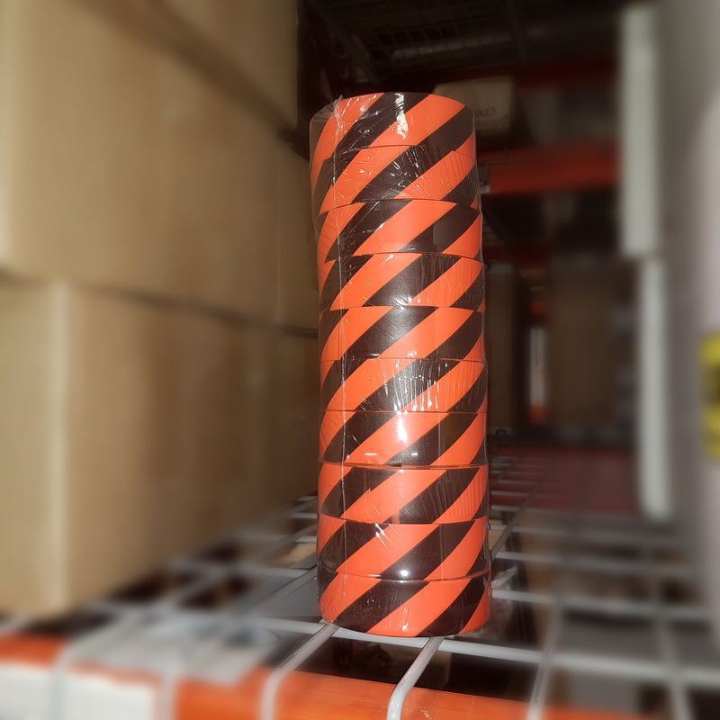 A Roll Of Orange Striped Flagging Tape