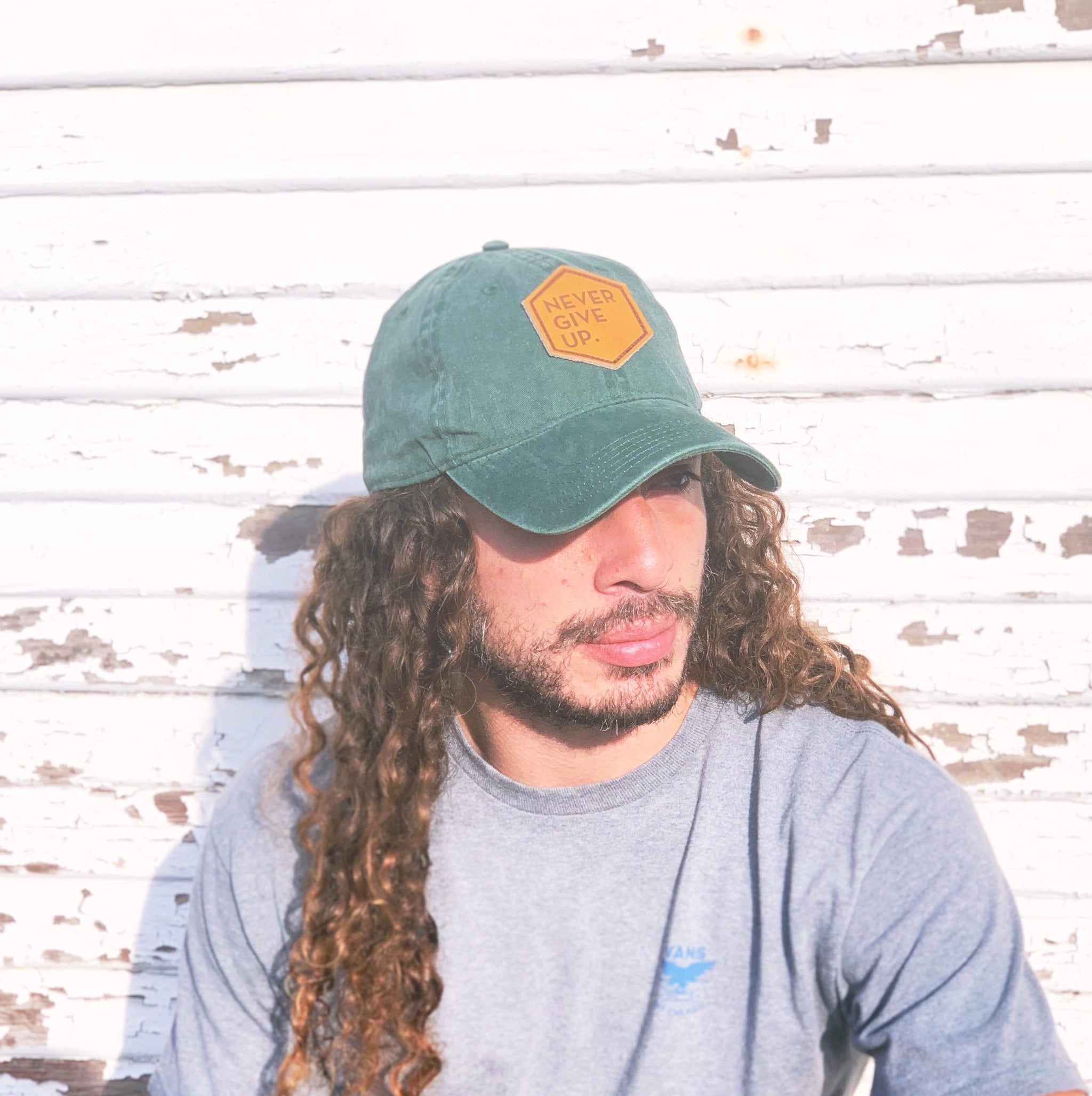 Man wearing green NEVER GIVE UP. leather patch hat