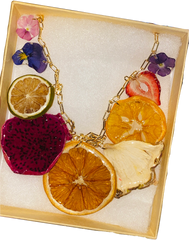A Maddy Sprout fruity necklace sits in a small cardboard box. It has a gold chain with an array of real fruit on it.