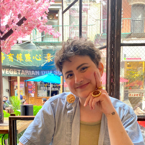 Maddy, with brown hair, light skin and wearing a blue denim button down with a green tank top underneath, sits in a restaurant smiles into the camera. They are wearing a ring and earrings with real lemons on them. The photo is cropped, showing just the upper half of their body.