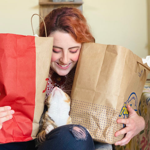 Maddy, with rose gold tones hair and rosey cheeks sits in a chair with their cat Lady on their lap. Maddy is holding two full paper bags around Lady. Lady and Maddy Look at each other. Maddy has a huge smile on their face.