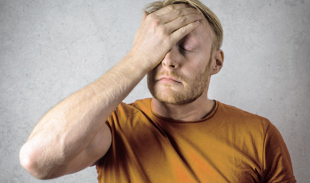 Man facepalming after vaping accident