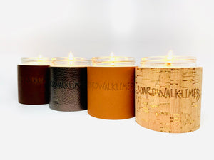 High end lit soy candles with designer cork and leather sleeves in caramel leather, cork with gold inlays, metallic pewter leather, and dark brown Teton leather all with custom brands