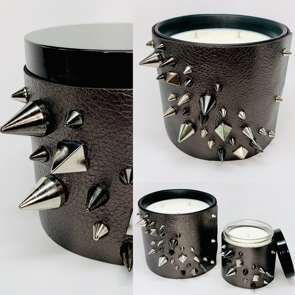 Luxury soy candle with one wick in a metallic gunmetal grey leather sleeve with silver and black studs in a cone and pyramid shape, 3-wick large soy candle with the metallic gunmetal leather wrap and black and silver studs in cone and pyramid shapes
