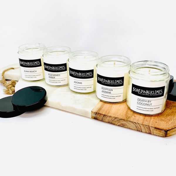 Five luxury 4oz soy candles in a sample flight in clear glass jars with shiny black lids
