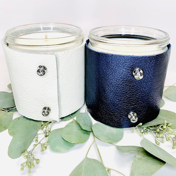 Two 16 oz soy scented candles, one in a fine white leather sleeve and one in s metallic sapphire leather sleeve with two shiny silver button studs