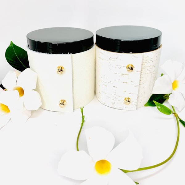 2 Luxury floral soy candles in topical plumeria and beautiful rose and gardenia scented candles wrapped in fine white leather and white cork with gold button studs with black shiny candle lids