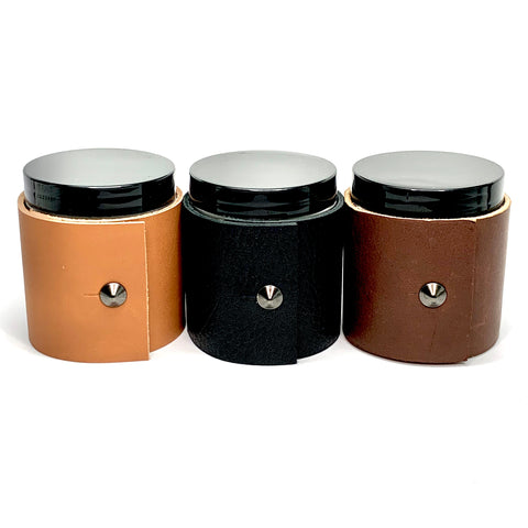 Three 4 oz candles in masculine scents wrapped in dark brown Teton leather, textured black leather, and caramel colored fine leather with oil rubbed black studs