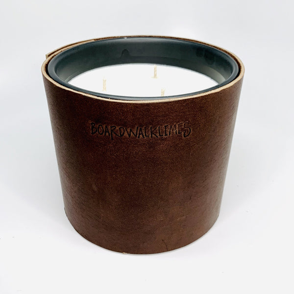 Luxury masculine soy candle wrapped in rugged dark brown Teton leather sleeve with oil rubbed black studs