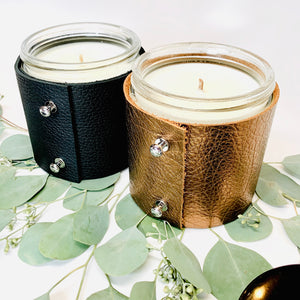 Two 16 oz luxury soy scented candles, one in textured black leather and one in metallic bronze leather with shiny silver button studs