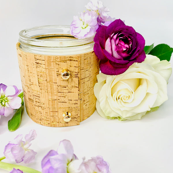 Beautiful floral soy candle with rose, gardenia, and lilac wrapped in a textured cork sleeve with gold inlays and 3 rose gold colored button studs