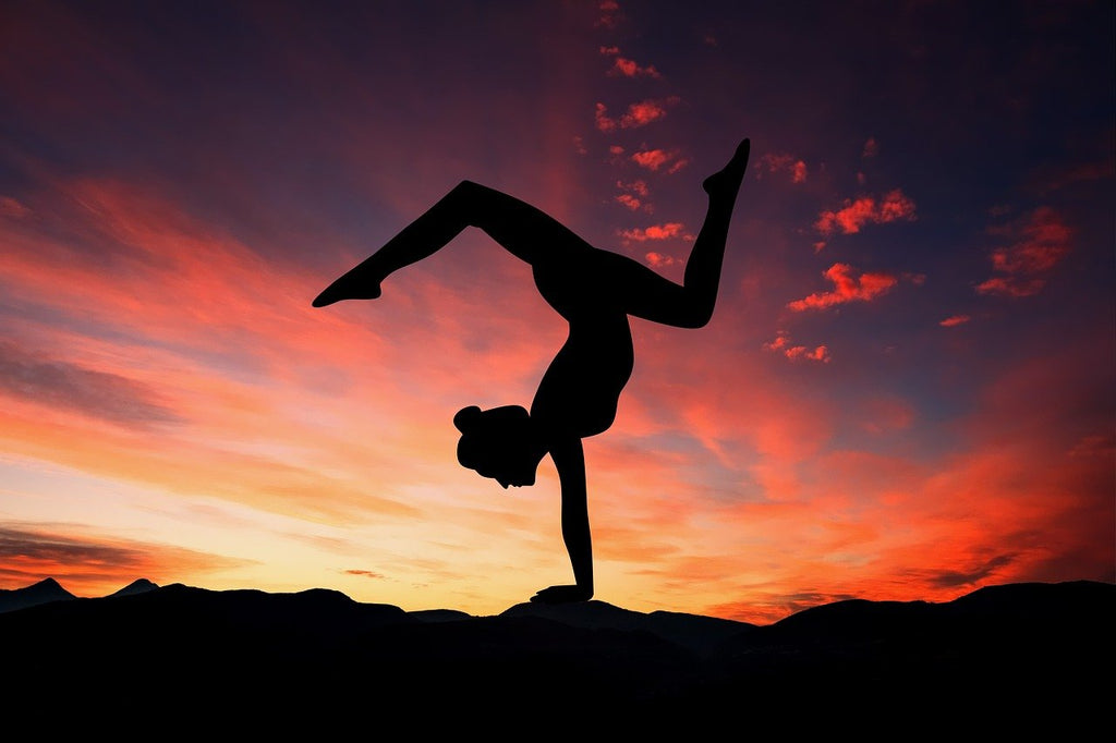 A silhouette of a woman in a yoga pose set against a beautiful sunset.