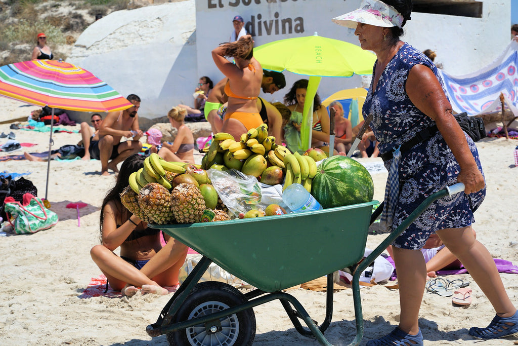 Woman pushing wheelbarrow of fruit for sale on beach.