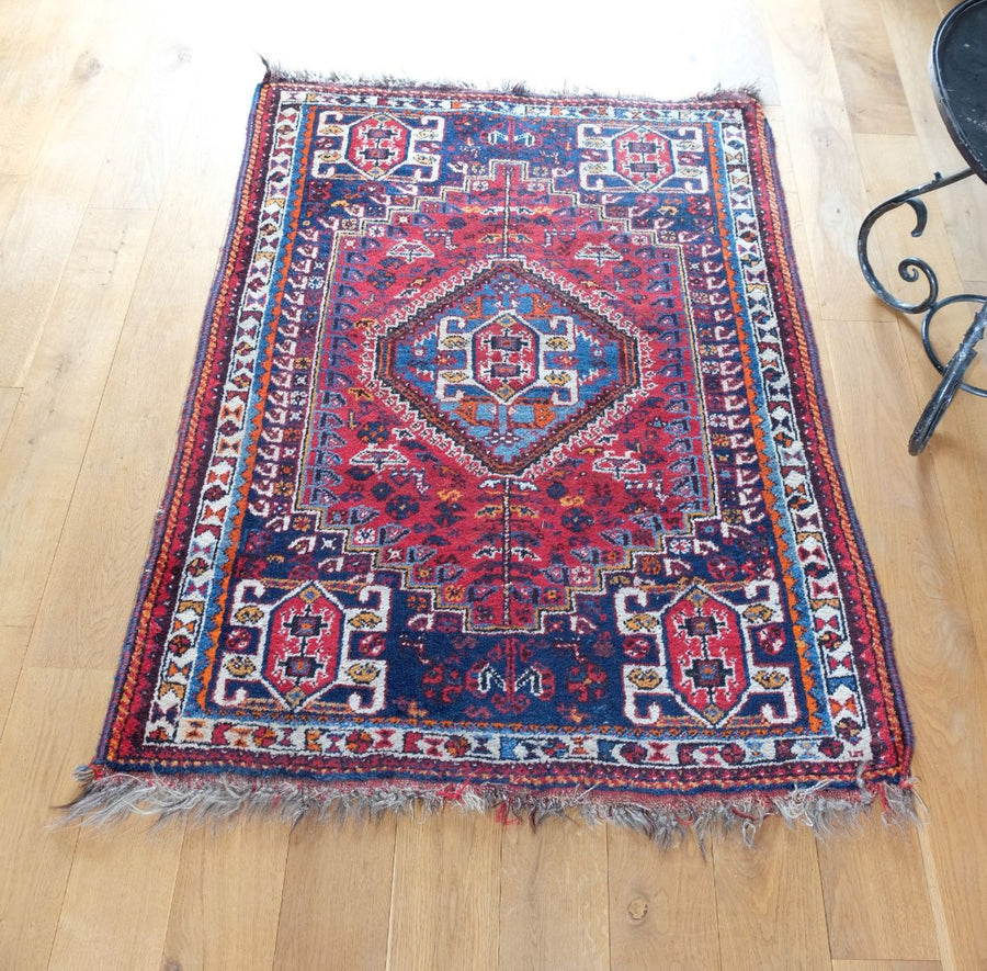Vintage Persian handmade rug with a vibrant red & blue ground