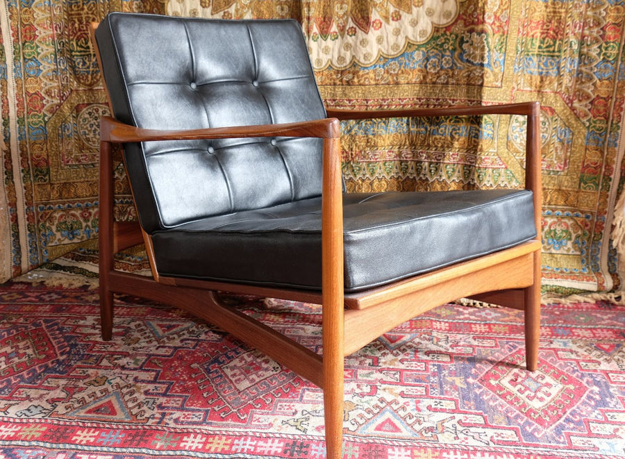 Rare Ib Kofod Larsen teak open armchair with black button backed cushions on the seat & back rest.