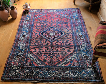 Handmade Malay rug with a red ground and surround by motifs