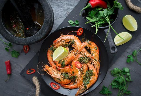 head on prawns on a plate with a pestle and mortar