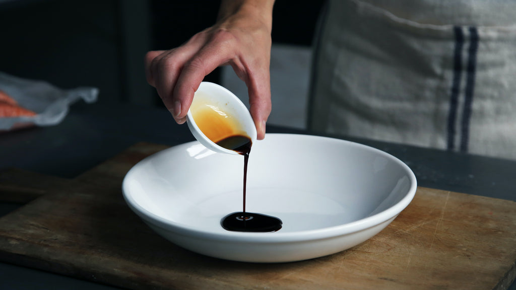 white plate with someone pouring balsamic vinegar on it