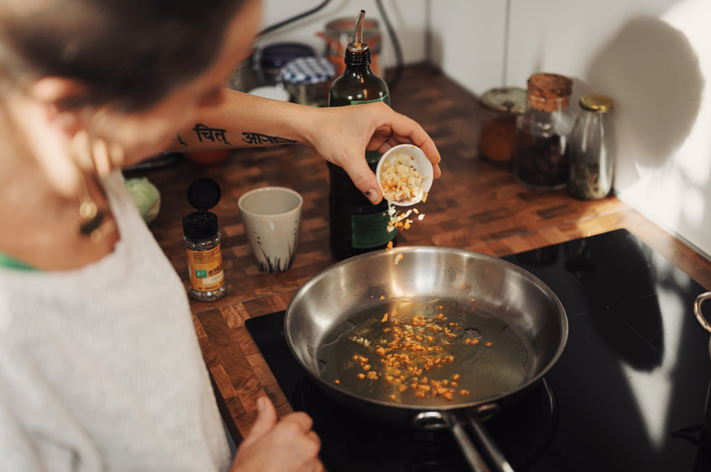 man adding garlic to a pan with oil